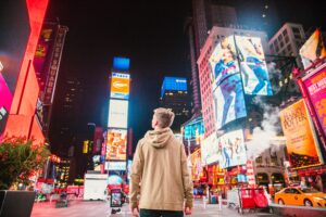 boy in times square new york looking at ads trying to change his buying behavior