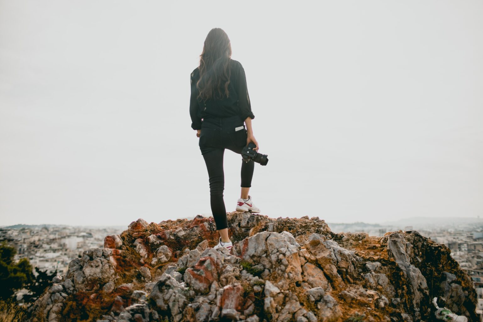 a woman on the top of a mountain with camera thinking about the essentials to become an influencer